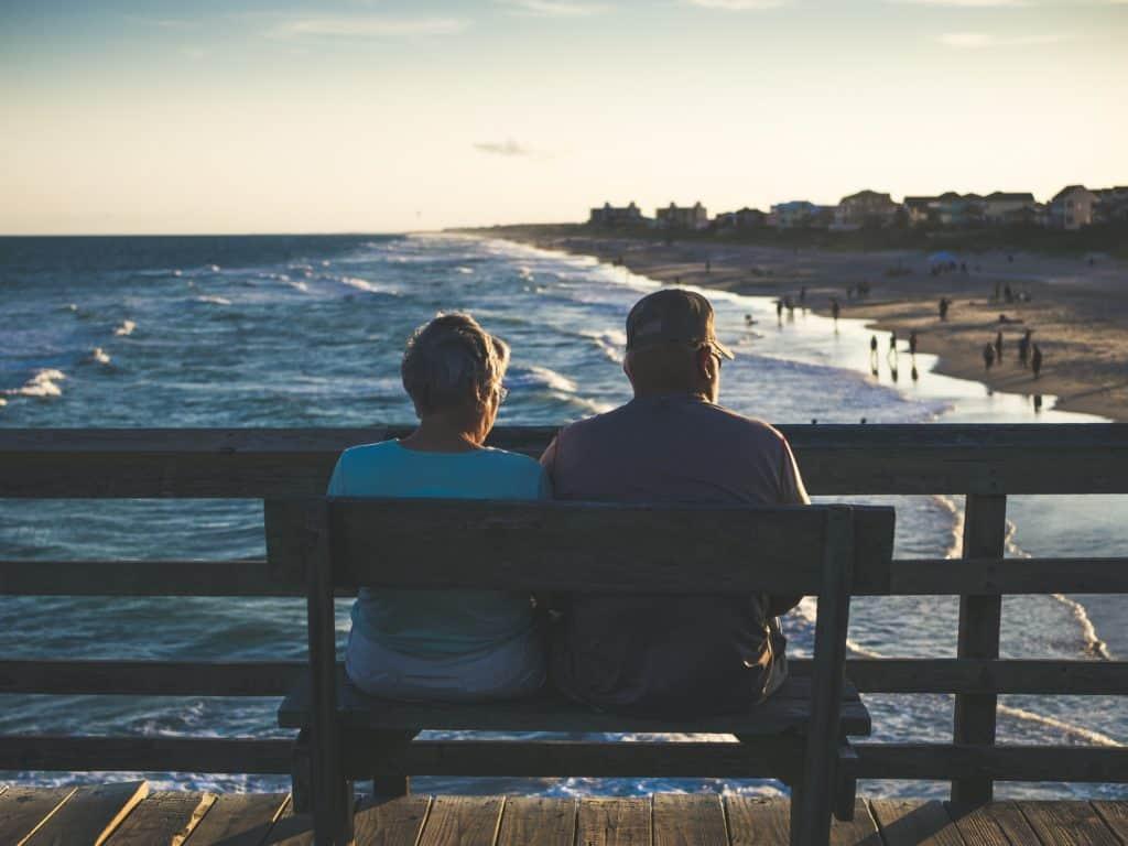 Elderly couple sitting by ocean