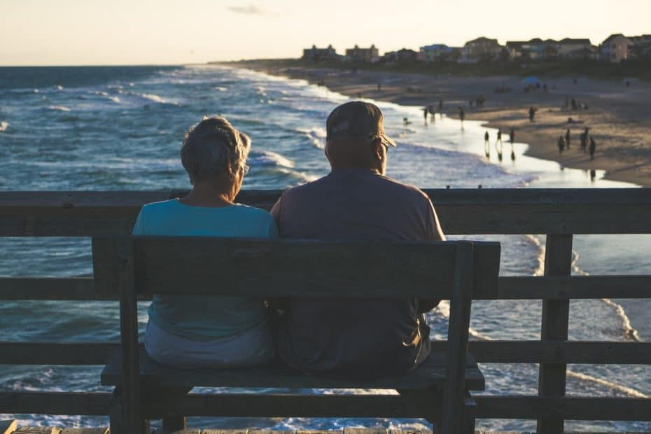 Elderly couple sitting by ocean