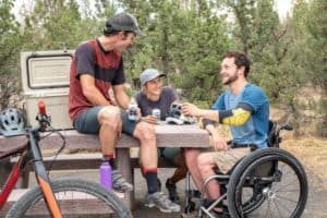 man in a wheelchair in the woods with friends